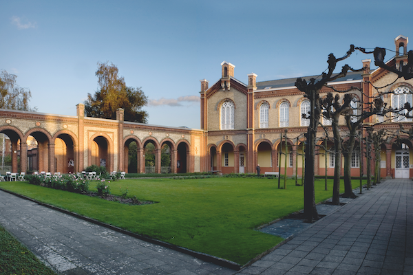 The museum's central court and one wing of the nineteenth-century buiding. The court has a green lawn, several trees, roses and a terrace. © 2012, Guido Suykens.